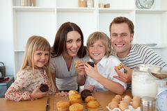 Nette Kinder, die Muffins mit ihren Muttergesellschaftn essen stockbilder