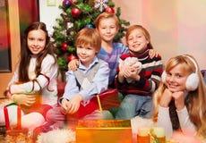 Nette Kinder, die nahe Weihnachtsbaum sitzen Lizenzfreie Stockfotos