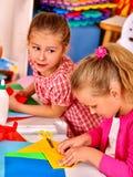Nette Kinder, die Origamiflugzeug im Kindergarten halten stockfotografie