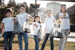 Nette nette Kinder, die Sänftentaschen halten Lizenzfreies Stockbild