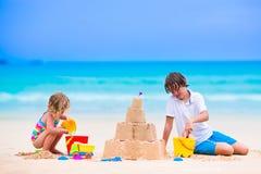 Nette Kinder, die Sandburg auf dem Strand errichten Stockfotografie