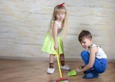 Nette Kinder, die Spielzeugbesen und -Müllschippe verwenden stockbild