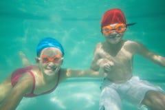 Nette Kinder, die unter Wasser im Pool aufwerfen Lizenzfreie Stockfotos