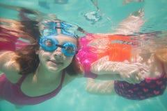 Nette Kinder, die unter Wasser im Pool aufwerfen Stockbilder