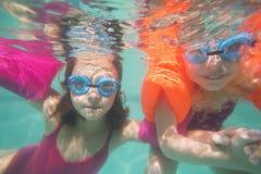 Nette Kinder, die unter Wasser im Pool aufwerfen Lizenzfreies Stockbild