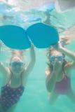 Nette Kinder, die unter Wasser im Pool aufwerfen Stockfotografie