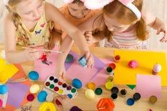 Nette Kinder, die zu Hause Ostereier malen stockfotos