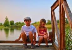 Nette Kinder, kleiner Junge und Mädchen sitzen auf Pier am Sommerabend Zwei Geschwister Goldene Stunde durch den Seeufer Glücklic stockbild