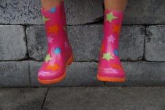 Nette Kinderbeine in den Gummistiefeln an einem regnerischen Tag Lizenzfreie Stockbilder