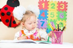 Nette Kindermädchenzeichnung mit bunten Bleistiften in der Vorschule bei Tisch im Kindergarten Stockbild