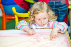 Nette Kindermädchenzeichnung zeichnet sich entwickelnden Sand in der Vorschule bei Tisch im Kindergarten Lizenzfreie Stockfotografie