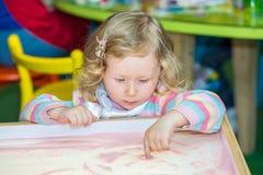 Nette Kindermädchenzeichnung zeichnet sich entwickelnden Sand in der Vorschule bei Tisch im Kindergarten stockbilder