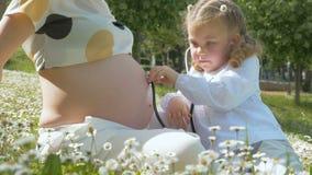 Nette Kinderspiele behandeln, junger Spezialist überprüft eine schwangere Frau stock video footage