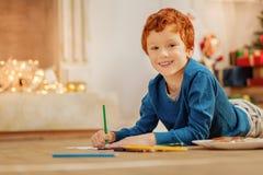 Nette Kinderzeichnung und Lächeln in Kamera Stockbild