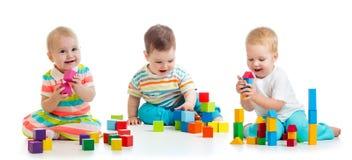 Nette kleine Babys, die mit Spielwaren oder Blöcken spielen und Spaß beim Sitzen auf dem Boden lokalisiert über weißem Hintergrun stockfotos