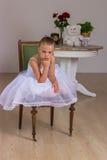 Nette kleine Ballerina in einem weißen Kleidersitzen lizenzfreie stockbilder