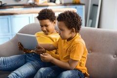 Nette kleine Brüder, die zusammen Karikatur auf Tablette aufpassen Lizenzfreie Stockfotos