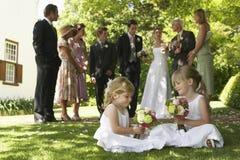 Nette kleine Brautjungfern, die Blumensträuße im Garten halten Stockfotografie