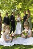 Nette kleine Brautjungfern, die Blumensträuße im Rasen halten Lizenzfreies Stockfoto