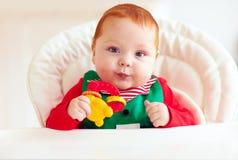 Nette kleine Elfe, Säuglingsbaby, das im Highchair sitzt Stockfoto
