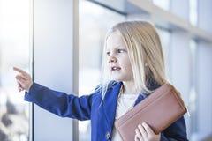 Nette kleine Geschäftsfrau, die auf Fenster im Bürogebäude zeigt Lizenzfreie Stockbilder