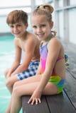 Nette kleine Geschwister, die Poolside sitzen Lizenzfreies Stockfoto
