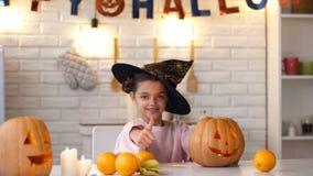Nette kleine Hexe, die an Halloween-Partei mit dem Steckfassungskürbis zeigt Daumen-oben sitzt stockfoto