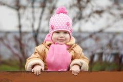 Nette kleine 2 Jahre alte Mädchen, die auf der Bank sitzen Lizenzfreies Stockfoto