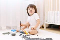 Nette kleine 2 Jahre Junge mit Bürsten- und Gouachefarben zu Hause Stockfotos
