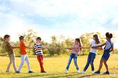 Nette kleine Kinder, die draußen mit Seil spielen lizenzfreie stockfotografie