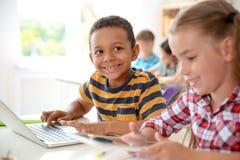 Nette kleine Kinder mit den Geräten, die am Schreibtisch sitzen lizenzfreie stockfotos