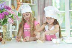 Nette kleine Mädchen in den Chefhüten, die Teig machen Lizenzfreies Stockfoto