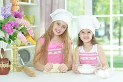 Nette kleine Mädchen in den Chefhüten, die Teig machen Lizenzfreies Stockbild