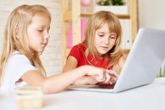 Nette kleine Mädchen, die Laptop verwenden lizenzfreie stockfotos
