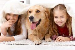 Nette kleine Mädchen, die Spaß mit Hundedem lächeln haben Stockbilder