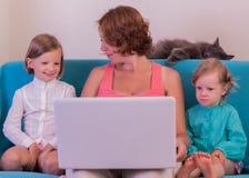 Nette kleine Mädchen mit der Mutter, die den Laptop aufpasst Lizenzfreies Stockbild