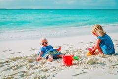 Nette kleine Mädchen spielen mit Sand auf Strand stockfoto