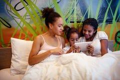 Nette kleine Mädchen und ihre Mutter, die auf einem Bett liegt stockfotos
