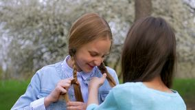 Nette kleine Schulmädchen blond und braun Frisuren draußen tun flechtender Zopf stock footage