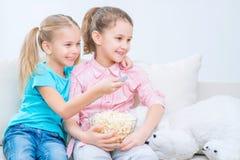 Nette kleine Schwestern, die auf dem Sofa sitzen Stockfotografie