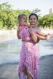 Nette kleine Schwestern im rosa korallenroten Kleid, das im fontaine spielt Lizenzfreies Stockfoto