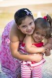 Nette kleine Schwestern im rosa korallenroten Kleid, das im fontaine spielt Lizenzfreie Stockbilder