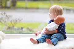 Nette kleine Tanne, die mit Puppe spielt Lizenzfreie Stockfotos