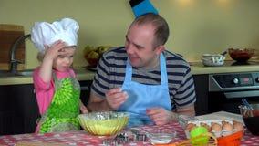 Nette kleine Tochter mit glücklichem hübschem Vater setzte Mehl auf die Nase und mischte Mehl stock video footage