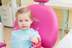 Nette kleines Mädchen sitts im zahnmedizinischen Stuhl im Zahnarztbüro, Nahaufnahmeporträt stockfotografie