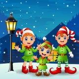 Nette Kleinkindelfen mit den Schneefällen, die am Nachthintergrund fallen Stockfotos