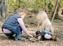 Nette Kleinkinder, die mit trockenen Stöcken auf dem Boden spielen stockfotografie