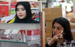 Nette Kosmetikfrau, die Spaß mit kosmetischen Produkten hat Stockbild