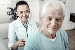 Nette nette Krankenschwester, die den Patienten und das Lächeln überprüft Lizenzfreie Stockbilder