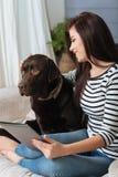 Nette lächelnde Frau abgelenkt durch ihren netten Hund Lizenzfreie Stockfotografie